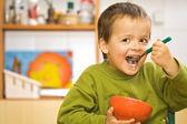 Niño feliz comiendo el desayuno - cereales y leche — Foto de Stock