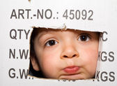 Bored kid peeking out from a cardboard box — Stock Photo