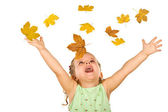 Happy shouting little girl with falling autumn leaves — Stock Photo