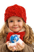 Little girl with a handful of snow and christmas bauble — Stock Photo