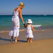 Woman and little girl walking on the beach — Stock Photo
