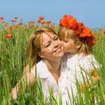 Little girl kissing her mother on the poppy field — Stock Photo