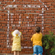 Two kids drawing a home — Stock Photo