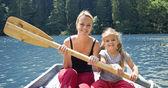 Donna e bambina sul lago in una piccola barca — Foto Stock
