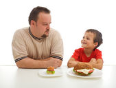 Man and young boy rival over food — Stock Photo