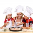 Stock Photo: Kids and their mother preparing a pizza