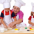 Grandmother teaching kids how to make cookies - Photo