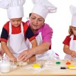 Grandmother teaching kids how to make cookies - Zdjęcie stockowe