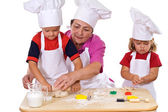 Grandmother teaching kids how to make cookies — Stock Photo