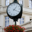 Old style street clock with flowers — Stock Photo