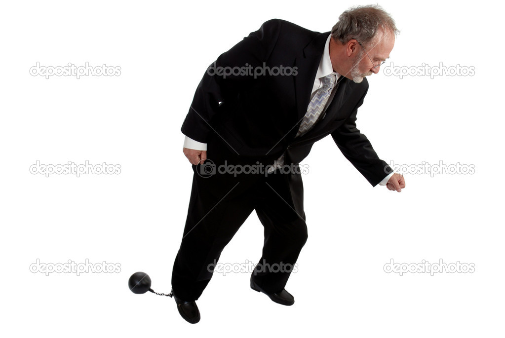 Businessman trying to move with a ball and chain attached to his leg   Stock Photo #6291676