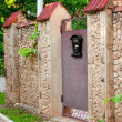 Stock Photo: Mail box hangs on ancient stone fence