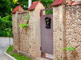 The mail box hangs on an ancient stone fence — Stock Photo
