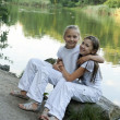 Two girls play at the lake - Stock Photo