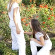 Two girls play with flowers in park — Stock Photo