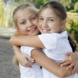 Little girl embraces the sister in park — Stock Photo