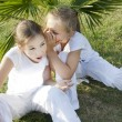 The little girl tells a secret to the friend — Stock Photo