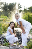 Two girls play at a fountain — Stock Photo