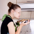 Young woman cooks dinner in the kitchen — Stock Photo