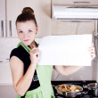 Stock Photo: Young woman holding a poster in the kitchen