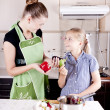 Young woman with a daughter in the kitchen preparing — Stock Photo #6678784