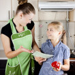 Foto Stock: Young woman with a daughter in the kitchen preparing