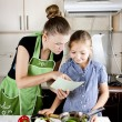 Stock Photo: Young woman with a daughter in the kitchen preparing