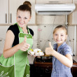 Foto de Stock  : Young woman with a daughter in the kitchen preparing