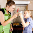 Young woman with a daughter in the kitchen preparing — ストック写真