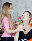 Daughter gives mother a flower — Stock Photo