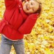 Autumn - the girl is in the yellow leaves — Stock Photo