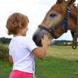 Young girl stroking horse — Stock Photo