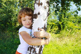Care for nature - little girl embrace a tree — Stock Photo