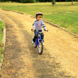 Little girl rides a bike in the park — Stockfoto