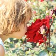 Girl smelling a large red rose — Stock Photo
