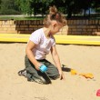 Young girl enjoys in the sandbox — Stock Photo