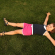 Young girl lie on green grass — Stock Photo