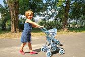A little girl with toy carriage — Stock Photo