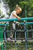 A girl walking on the ladder at the playground — Stock Photo