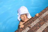 Young girl in the hat swims in the swimming pool — Stock Photo