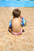 A little girl sitting by the pool — Stockfoto