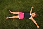 молодая девушка лежат на зеленой траве — Стоковое фото
