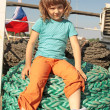 The girl sits on a thick coil of ropes - Stock Photo