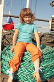 The girl sits on a thick coil of ropes — Stock Photo