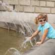 Girl playing with water from a fountain — Stock Photo