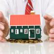 House on golden coins pile with businessman hands — Stock Photo