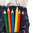Colored pencils in kids jeans pocket - Stock Photo