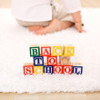 Royalty-Free Stock Photo: Child turning away from toy blocks - back to school theme