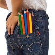 Child with color pencils in back pocket — Stock Photo