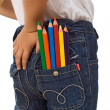 Child with color pencils in back pocket — Stockfoto